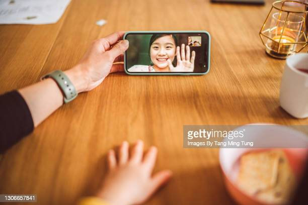 first person perspective of mom & daughter having video call with family while enjoying snacks on a dining table at home - flatten the curve stock pictures, royalty-free photos & images