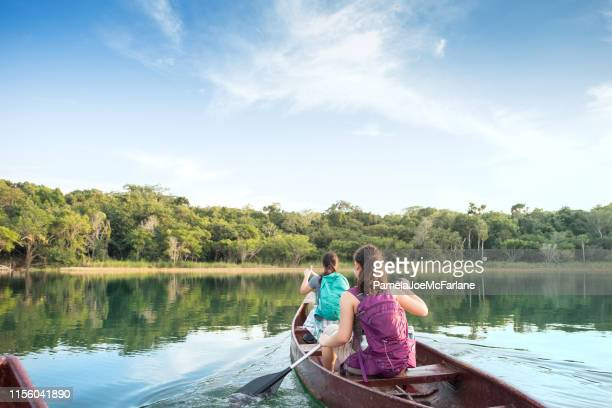first person perspective of sisters with backpacks canoeing in lake - camping stock pictures, royalty-free photos & images
