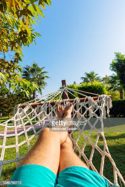 first person point view of a man relaxing in the hammock on a sunny day - first day of summer stock pictures, royalty-free photos & images