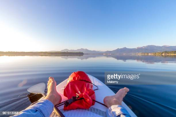 First person view from a paddling board at sunrise. Lake Chiemsee, Chiemgau, Bavaria, Germany