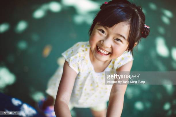 first person view of a person looking down at a lovely little girl in a playground - 歯を見せて笑う ストックフォトと画像