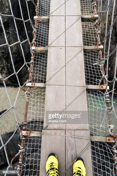 First person view of a tourist that crossing the Carrick-a-Rede rope bridge, Northern Ireland