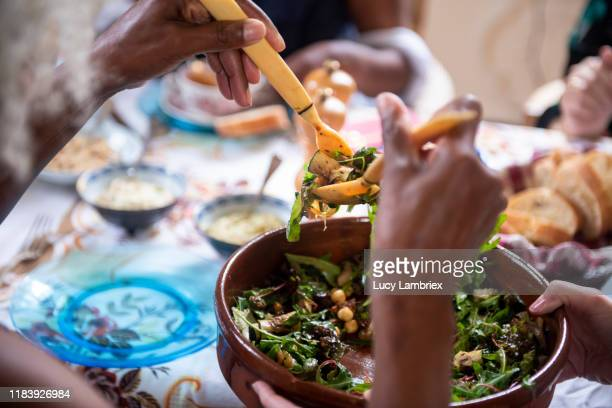 first person view of a woman serving salad at a vegan birthday lunch party - ready to eat stock pictures, royalty-free photos & images