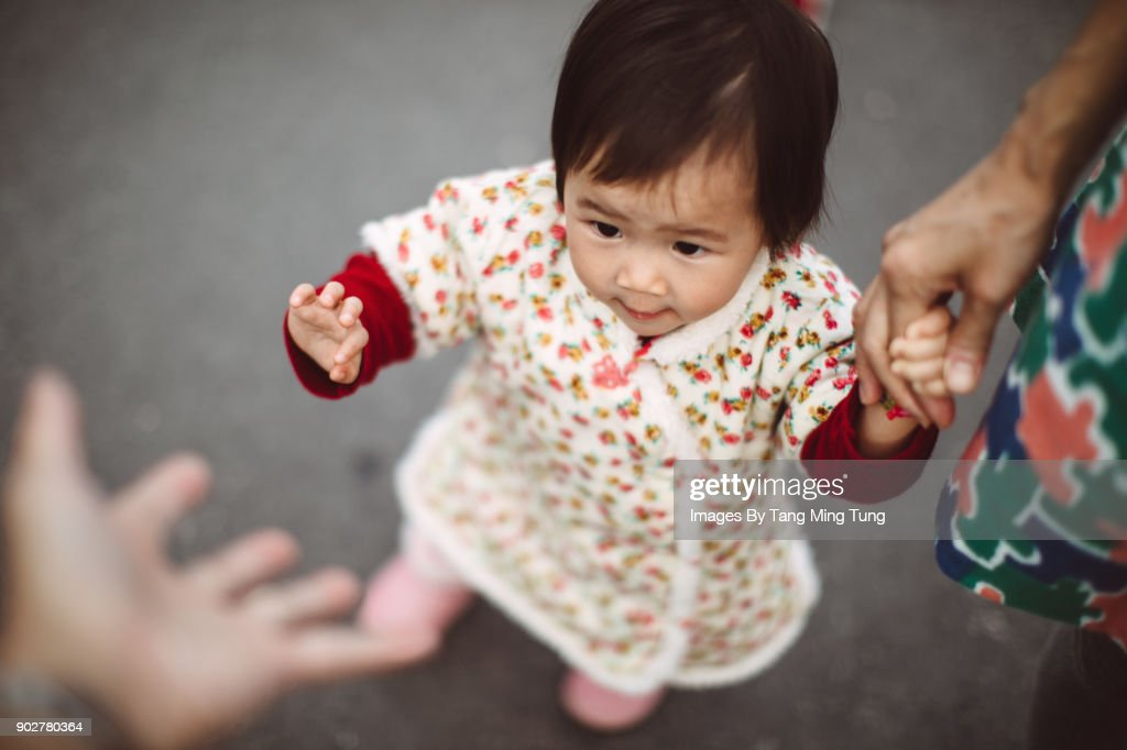 First person view of dad looking at his lovely little baby reaching out her little hand to himself. : Stock Photo