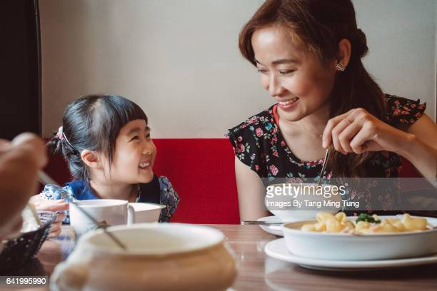 First person view of father having meal with pretty young wife and their lovely daughter joyfully in a restaurant.