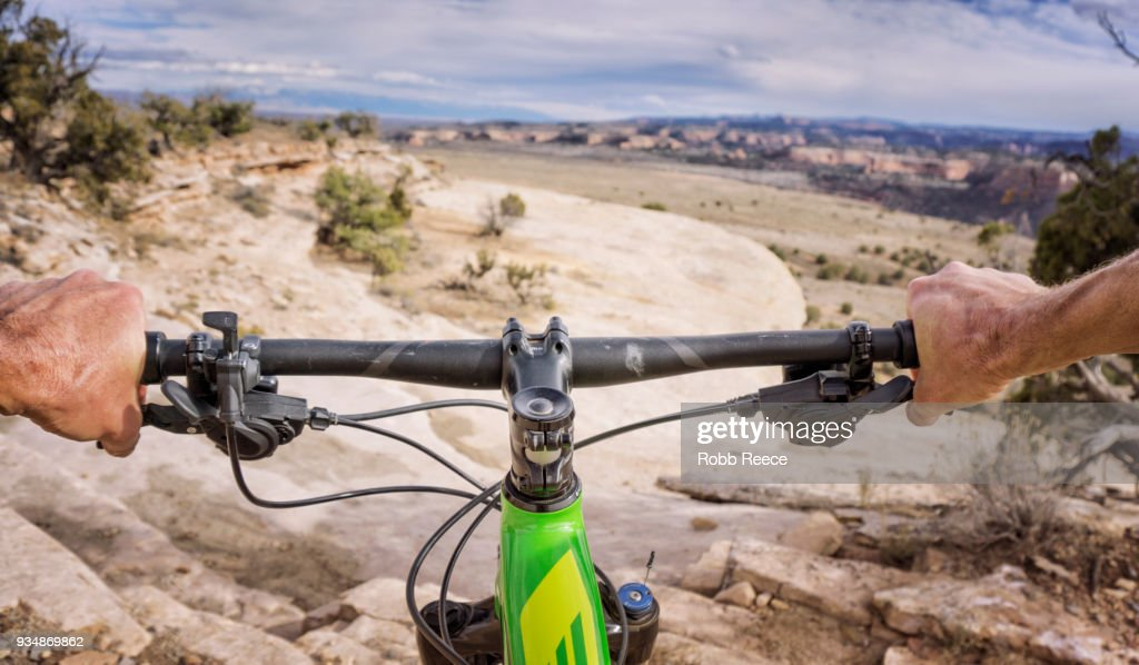 First person view of mountain biker on a desert trail : Stock Photo
