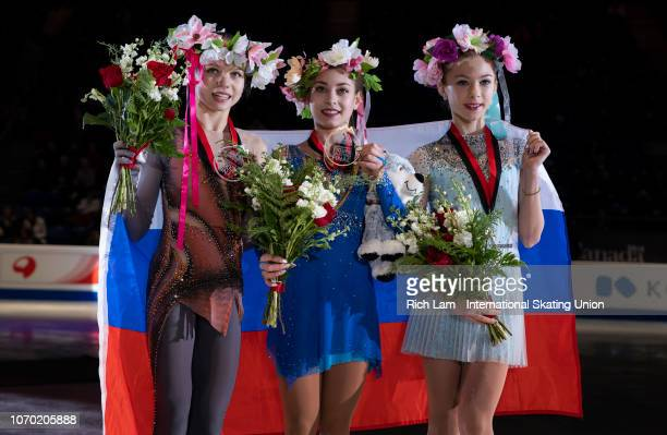 First place Alena Kostornaia of Russia second place Alexandra Trusova of Russia and third place Alena Kanysheva of Russia pose for photos with...