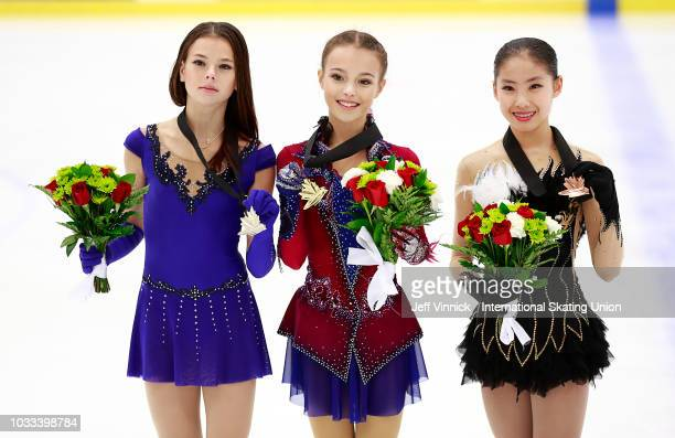 First place finisher Anna Shcherbakova of Russia stands between second place finisher Anastasia Tarakanova of Russia and third place finisher Rion...