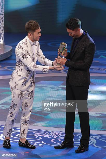 First place Jackson Lai receives trophy from Mr Hong Kong 2007 champion Benjamin Yuen during the Mr Hong Kong Pageant 2016 at TVB City on September...