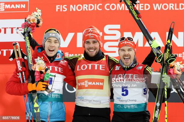First Place Johannes Rydzek of Germany second place Mario Seidl of Austria and third place Fabian Riessle of Germany celebrate during the flower...