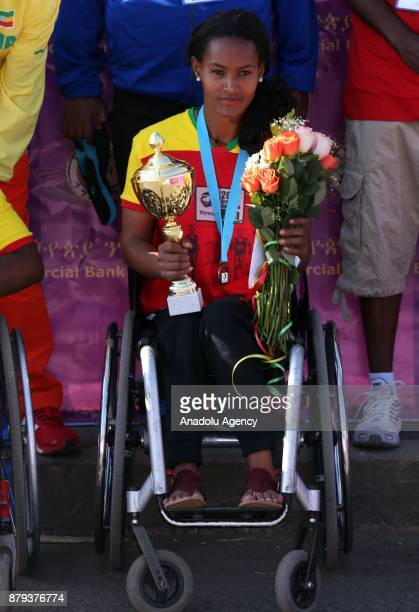 First place winner in women's Great Ethiopian Run disabled Ethiopian athlete Moris Getenet holds flowers and a trophy at Adwa Square in Addis Ababa...