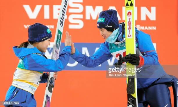 First place Yuki Ito and second place Sara Takanashi of Japan high five on the podium at the award ceremony for the Ladies Normal Hill during day one...