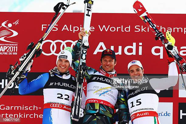 First placed Aksel Lund Svindal of Norway second placed Christof Innerhofer of Italy and third placed Peter Fill of Italy celebrate at the flower...