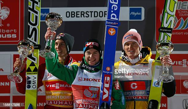 First placed Anders Jacobsen of Norway celebrates with second placed Gregor Schlierenzauer of Austria and third placed Severin Freund of Germany...