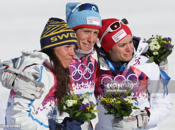 First placed Marit Bjoergen of Norway celebrates during the flower ceremony with second placed Charlotte Kalla of Sweden and third placed Heidi Weng...