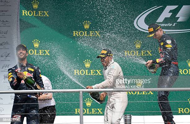 First placed Mercedes AMG Petronas F1 Team's British driver Lewis Hamilton celebrates on the podium next to second placed Red Bull Racing's...