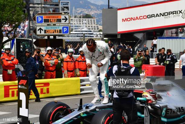 First placed Mercedes' British driver Lewis Hamilton celebrates winning the pole position after the qualifying session at the Monaco street circuit...