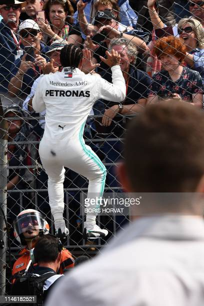 First placed Mercedes' British driver Lewis Hamilton jumps at a fence to greet fans as he celebrates winning the pole position after the qualifying...