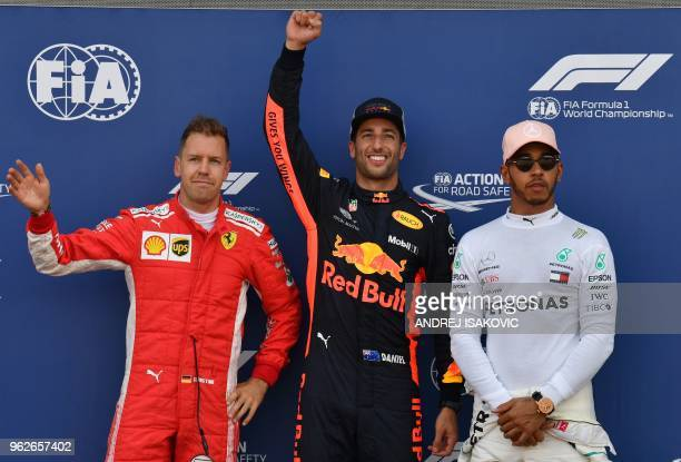First placed Red Bull Racing's Australian driver Daniel Ricciardo celebrates winning the pole position next to second placed Ferrari's German driver...
