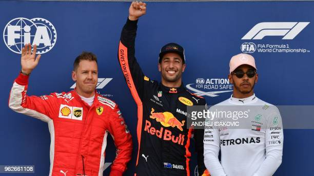TOPSHOT First placed Red Bull Racing's Australian driver Daniel Ricciardo celebrates winning the pole position next to second placed Ferrari's German...