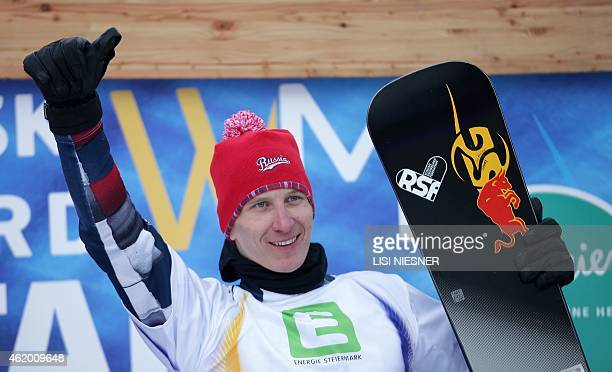 First placed Russia's Andrey Sobolev reacts on the podium after the Men's Snowboard Parallel Giant slalom finals at FIS Freestyle and Snowboarding...