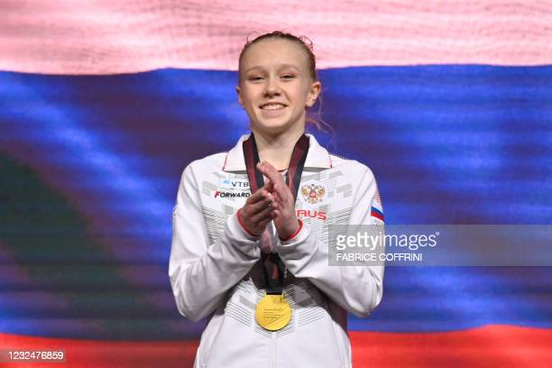 First placed Russia's Viktoriia Listunova celebrates with the gold medal on the podium during the award ceremony of the Women's all-around final of...