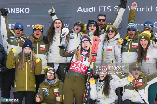 First placed US's Mikaela Shiffrin celebrates on the podium with her team after winning the women's Super-G event at the FIS ski alpine World Cup in...