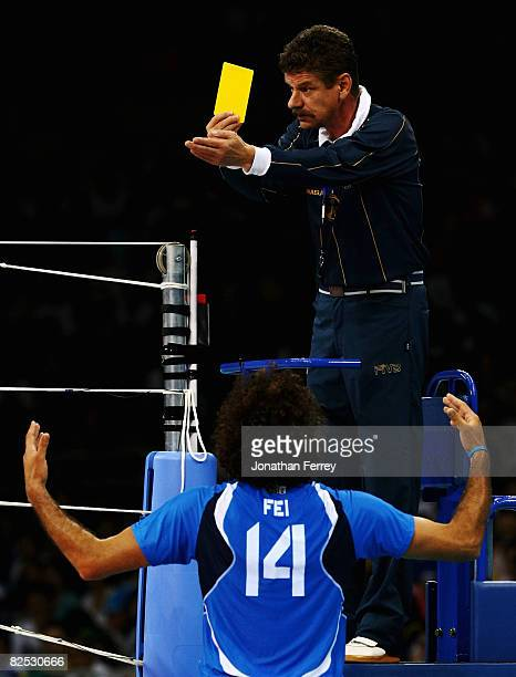 First referee Frank Leuthauser of Germany shows the yellow card as Alessandro Fei of Italy gestures in the Bronze Medal volleyball match between...