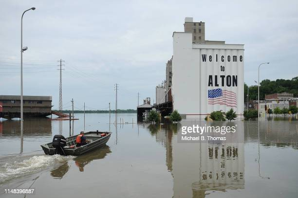A first responder drives a boat along a submerged road on June 6 2019 in Alton Illinois Residents along the Mississippi River are bracing for the...