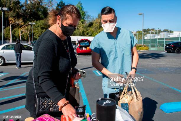 First responder Ivan Yniguez gets his gift bag from DPA president and organizer Nathalie Dubois-Sissoko at the Luxe hotel during the drive-through...