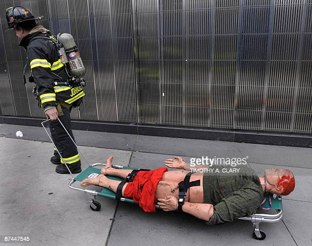 A first responder pulls a plastic dummy victim down the street during Operation Safe PATH 2009 May 17 2009 at the PATH station at the World Trade...
