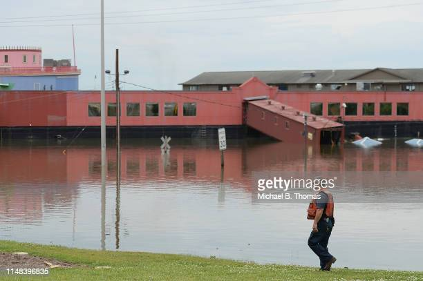 A first responder walks along a submerged road on June 6 2019 in Alton Illinois Residents along the Mississippi River are bracing for the expected...