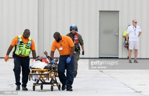 First responders escort an injured person from Hurricane Dorian devastated Abaco Island at the Odyssey Avaiation after US CoastGuard evacuated people...