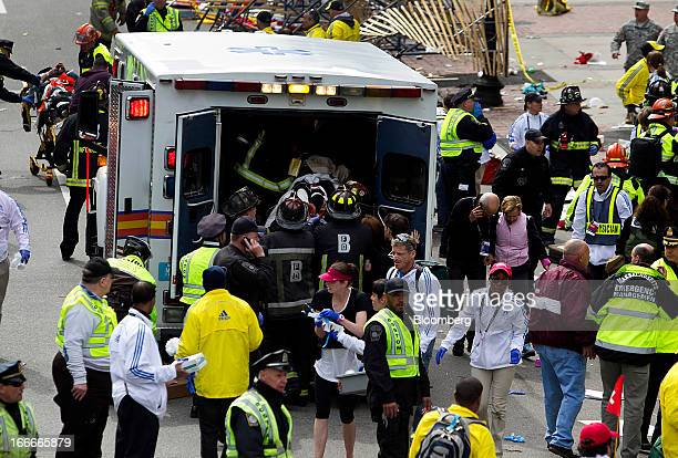 First responders load injured people into an ambulance where two explosions occurred along the final stretch of the Boston Marathon on Boylston...