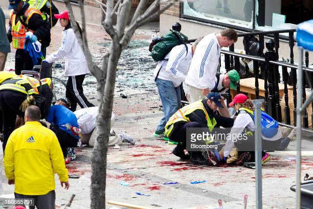 First responders rush to help injured people after two explosions occurred along the final stretch of the Boston Marathon on Boylston Street in...