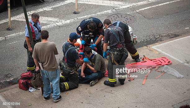 First responders stabilize and remove an accident victim in the Chelsea neighborhood of New York on Tuesday July 23 2013 The Uniformed Firefighters...
