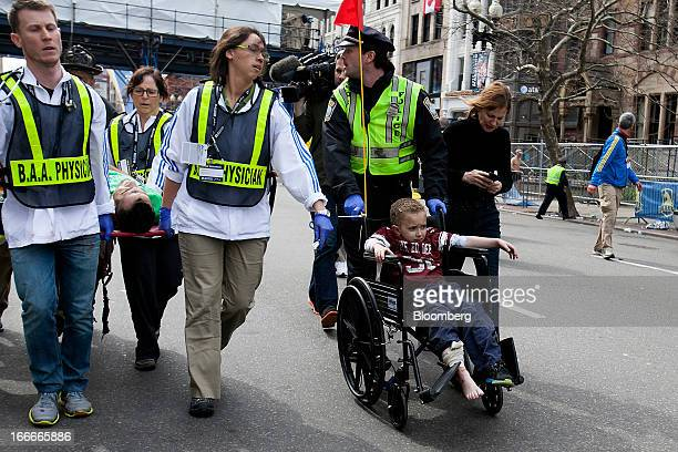 First responders tend to the wounded including a young boy in a wheelchair where two explosions occurred along the final stretch of the Boston...