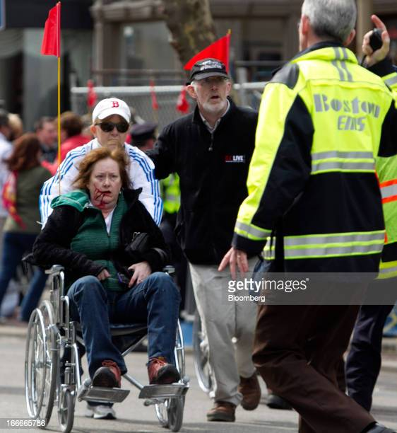 First responders transport an injured woman in a wheelchair where two explosions occurred along the final stretch of the Boston Marathon on Boylston...