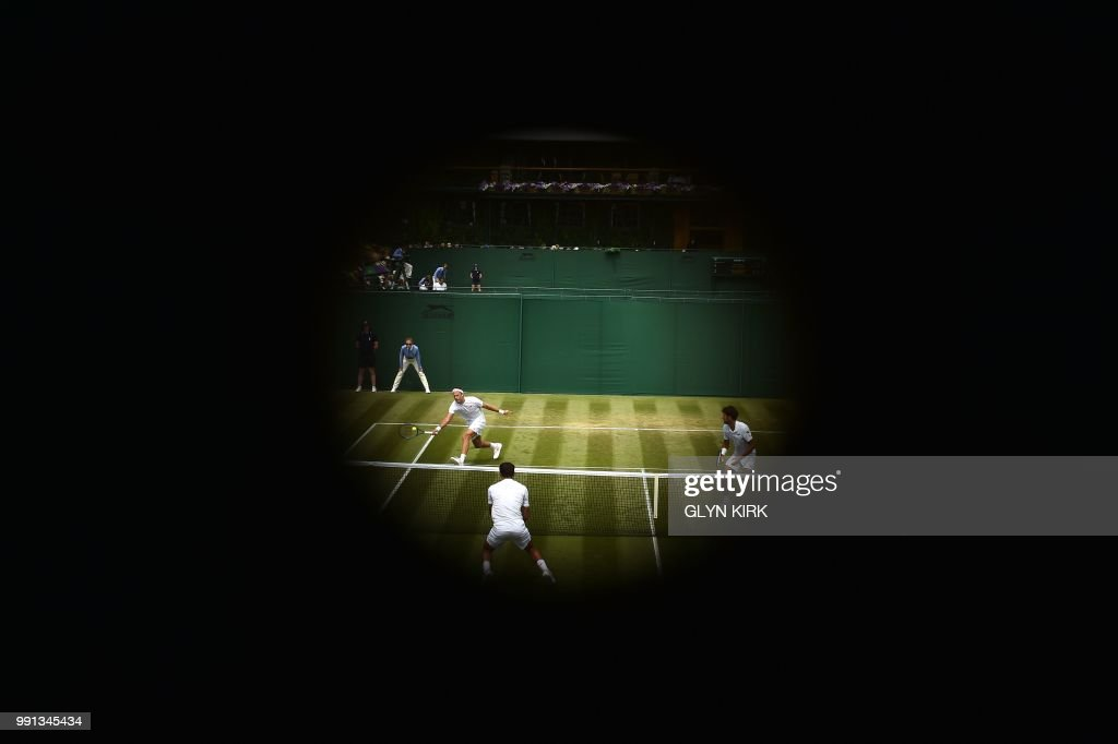 TOPSHOT - A first round doubles match takes place on court 10 on the third day of the 2018 Wimbledon Championships at The All England Lawn Tennis Club in Wimbledon, southwest London, on July 4, 2018. (Photo by Glyn KIRK / AFP) / RESTRICTED