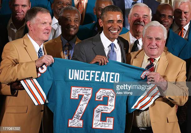 First row US President Barack Obama poses for photos with members of the 1972 Miami Dolphins including head coach Don Shula quarterback Bob Griese...