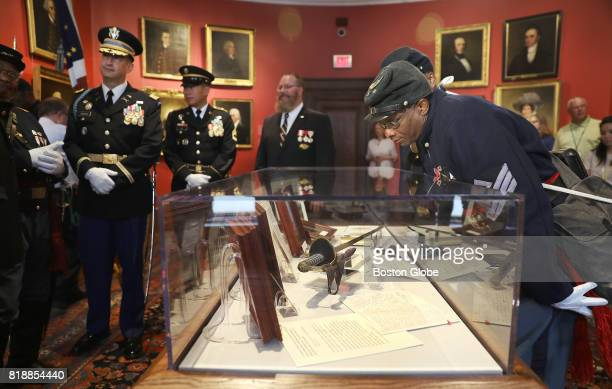 First Sgt Gerard Grimes takes a close look at the sword as members of the 54th Massachusetts Volunteer Regiment Company A are present for the...