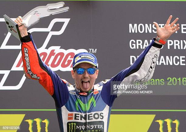 First Spain's rider Jorge Lorenzo celebrates on the podium after the MotoGP race of the French motorcycling Grand Prix on May 8 2016 in Le Mans...