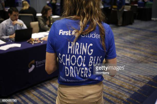A First Student Inc recruiter wears a tshirt with Hiring School Bus Drivers displayed on the back during a Job News USA career fair in Overland Park...