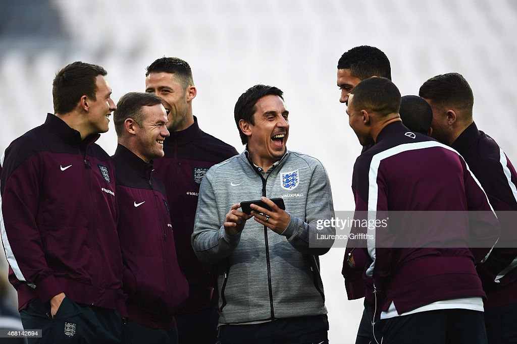 First Team Coach Gary Neville of England laughs with England players including Phil Jones (L) and Wayne Rooney (2ndL) during an England team stadium visit ahead of the International Friendly match against Italy at Juventus Arena on March 30, 2015 in Turin, Italy.