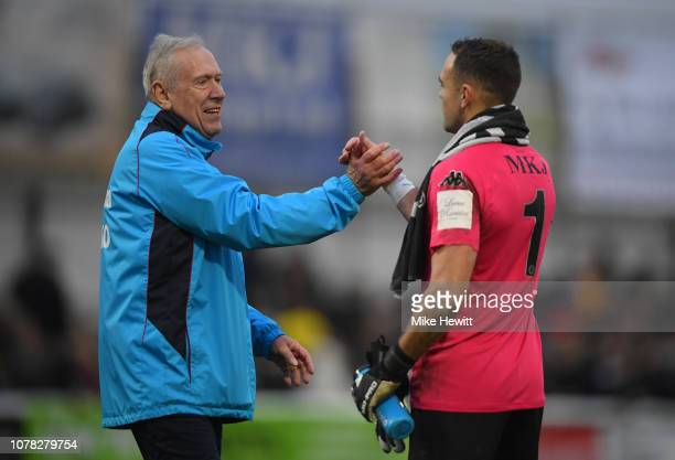 First team coach Martin Tyler embraces Craig Ross of Woking following the FA Cup Third Round match between Woking and Watford at Kingfield Stadium on...