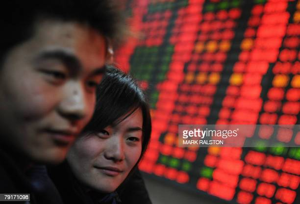 First time investors stand in front of a stock price board showing the red colour indicating rising prices at a private securities firm in Shanghai,...