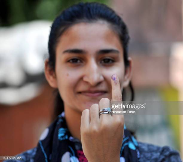 First time voter Madeeha Latif smilingly shows her index finger after casting her vote at a polling station at Circular Road on October 8 2018 in...