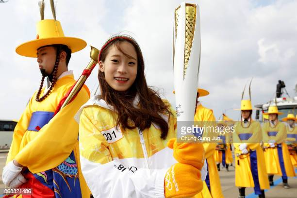 First torch bearer South Korean figure skater You Young holds the PyeongChang 2018 Winter Olympics torch during a torch relay on November 1 2017 in...