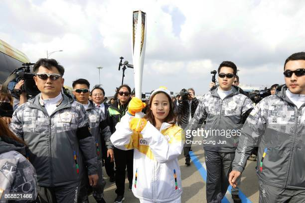 First torch bearer South Korean figure skater You Young runs as she hold the PyeongChang 2018 Winter Olympics torch during a torch relay on November...
