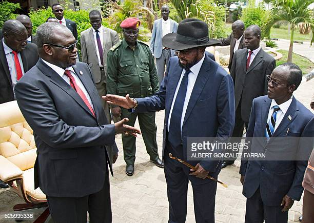 First Vice President of South Sudan and former rebel leader Riek Machar shakes hands with South Sudan President Salva Kiir flanked by Second Vice...